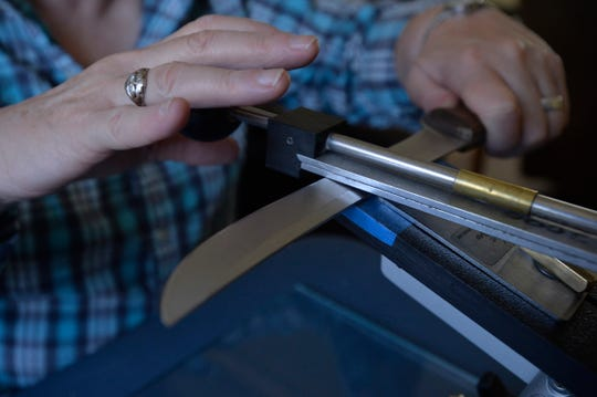 Sonja Bragstad sharpens knives and shears using an Edge Pro fixed angle knife sharpener.