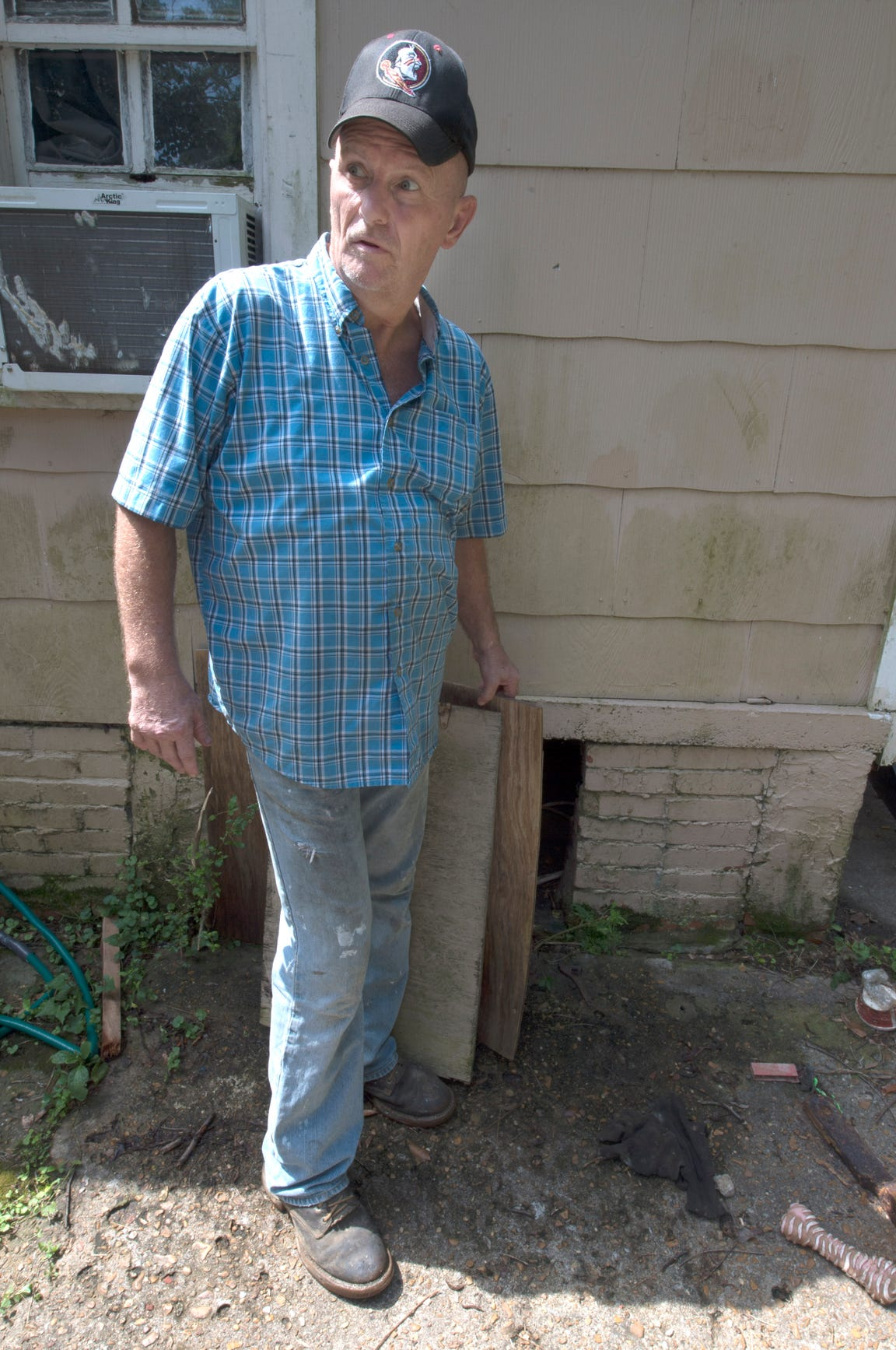 Jeffrey Armstrong pulls back the plywood to show the crawl space beneath his mother's former rental home. In 2001, he said he found .380-caliber automatic pistol in the space and thought it might have something to do with the quadruple murder at Tardy Furniture of 1996. A .380 gun was used in those killings, but no murder weapon was ever found. Thursday, July 19, 2018.