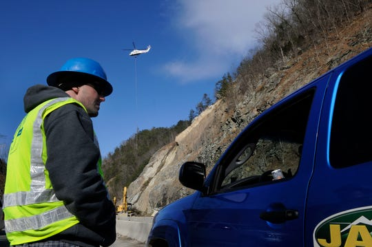 Phillips & Jordan, Inc. vice president and project manager Dudley Orr waits as workers use a helicopter Monday, Dec 28, 2009 to continue clearing trees from the site of a massive rock slide as they prepare to set drilling equipment. The drilling will install 590 steel rock bolts into the mountainside as a safety measure.