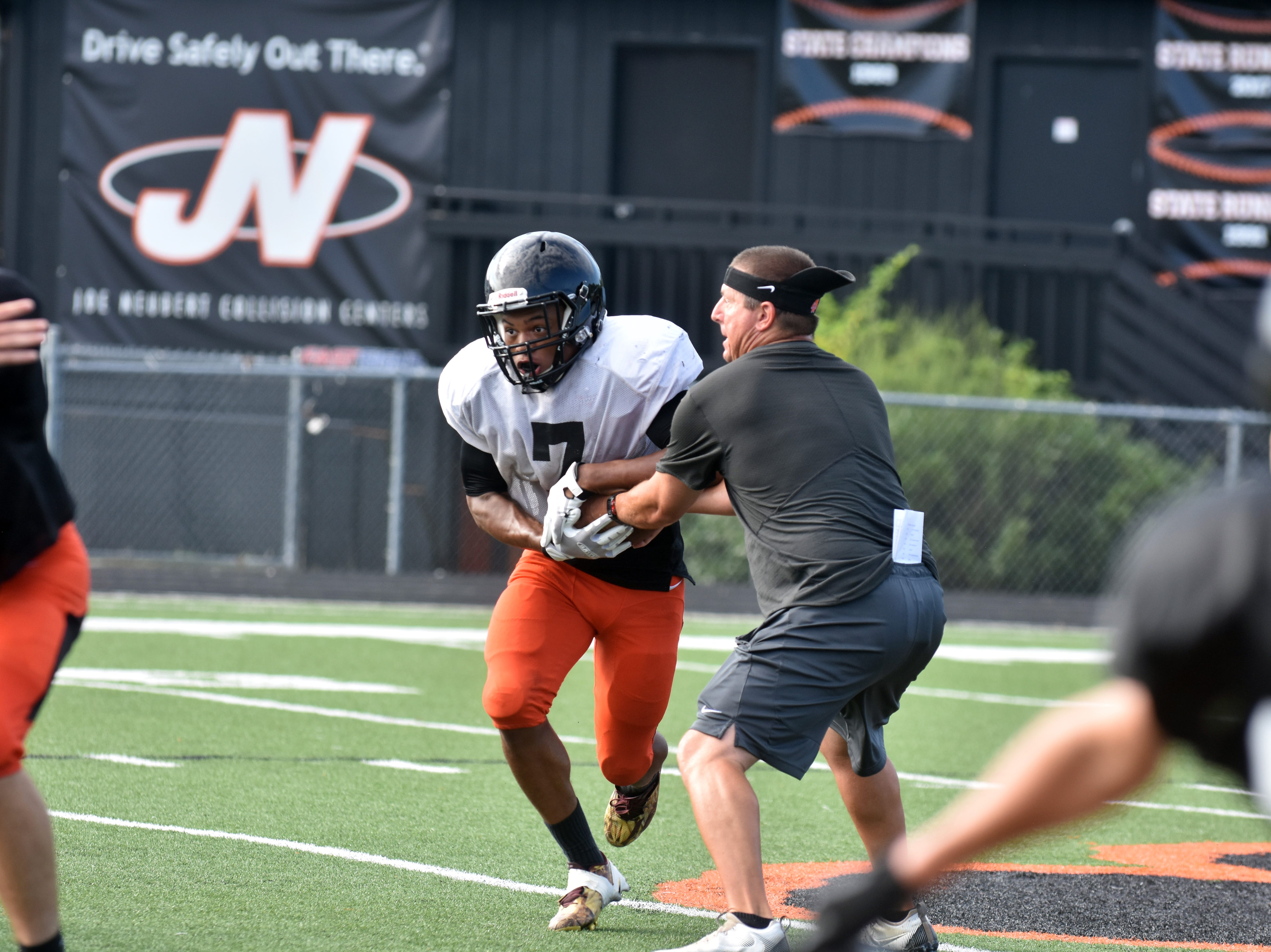 Powell High player Jordan Brown takes the hand-off from coach Matt Lowe during practice.