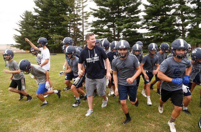 New Central Catholic head coach Brian Nay leads the Knights back out to the practice field after a water break Monday, July 30, 2018, at Central Catholic High School.