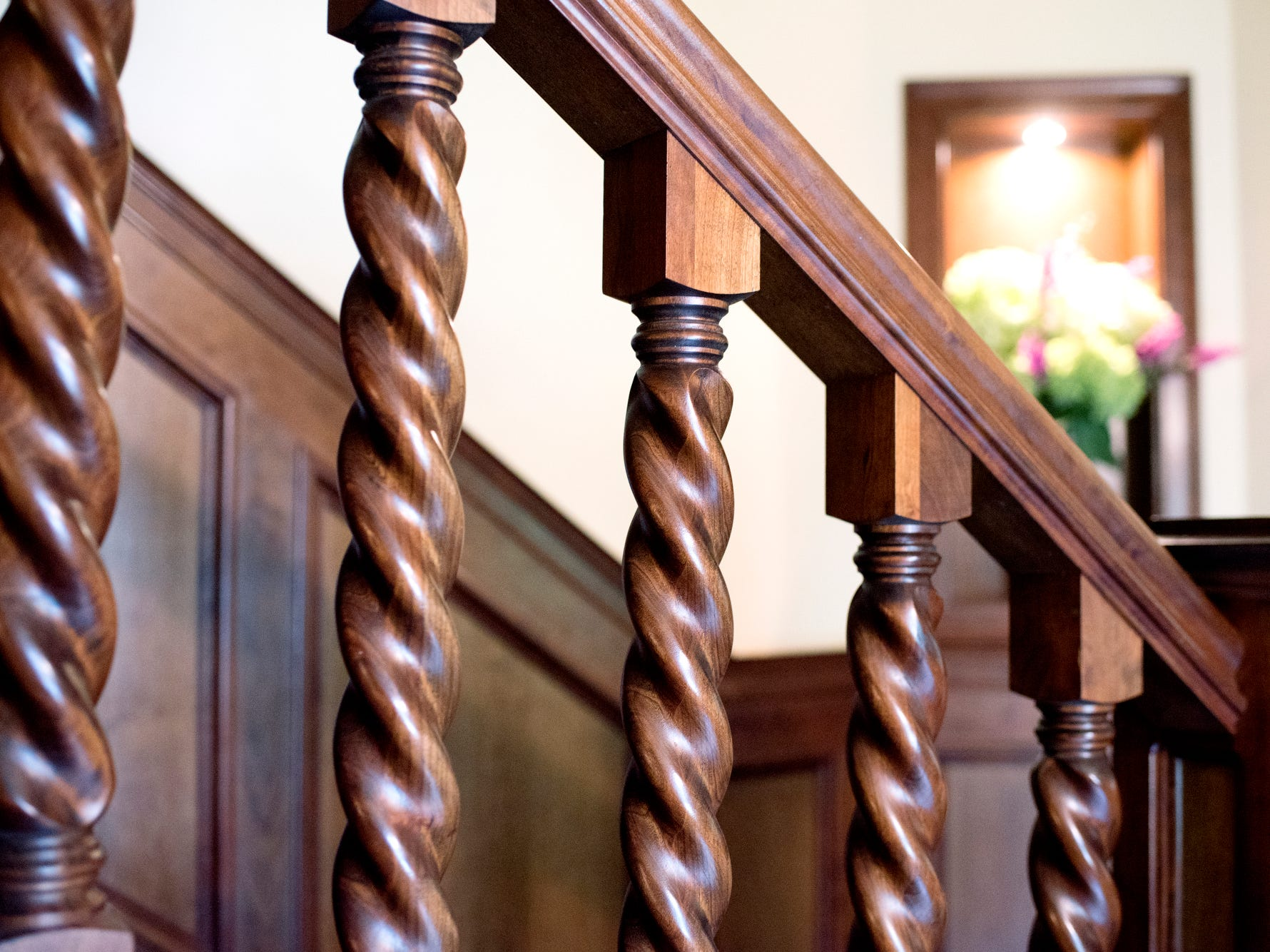 Decorative wooden railings line the stairs to the upper level inside Deb Atkinson's historically Colonial home photographed on Tuesday, July 24, 2018, in East Lansing. Built in 1930, the Colonial-style home surrounded by greenery and beautifully renovated is now on the market.