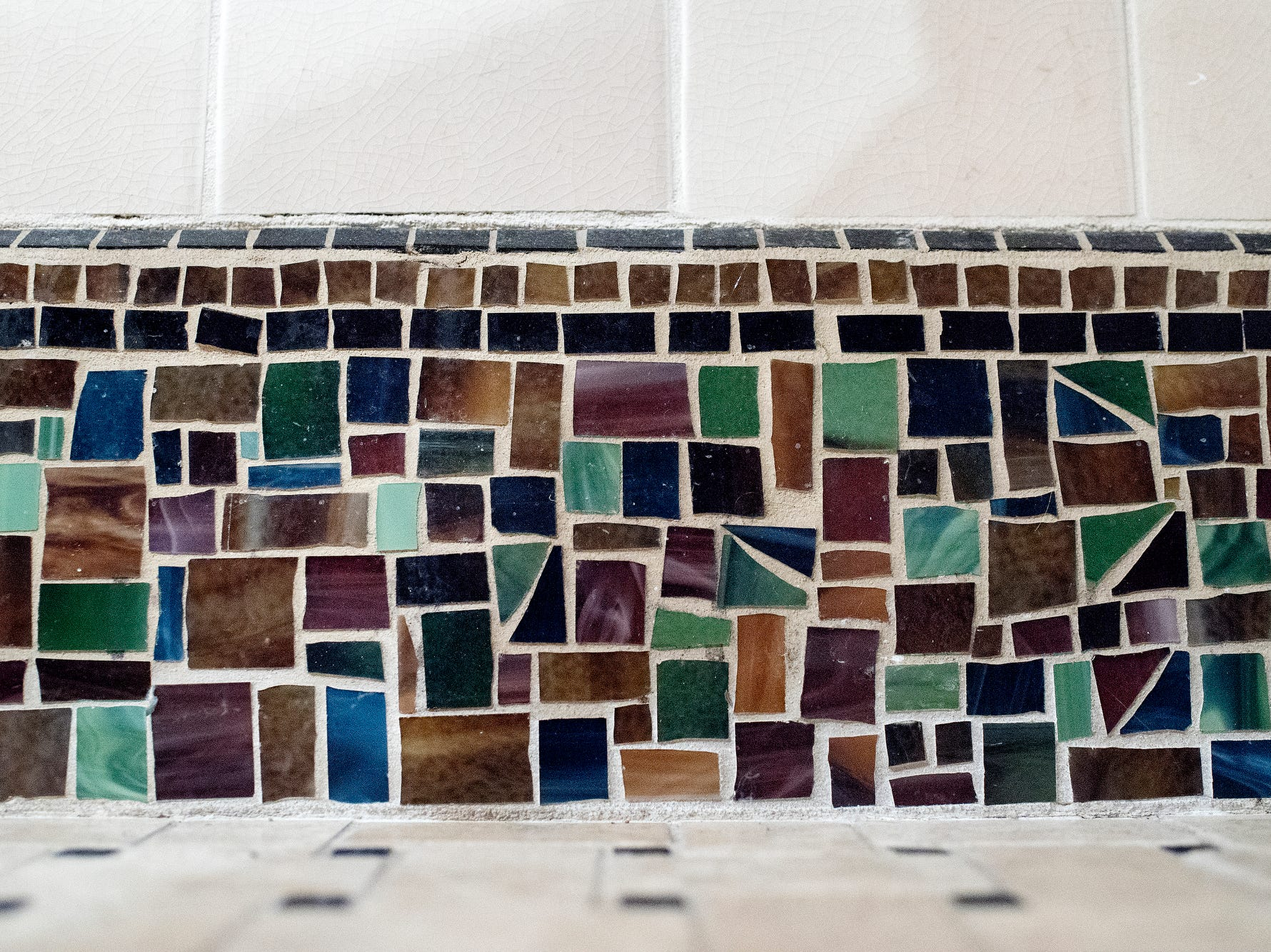 Deb Atkinson's mosaic work lines the bottom of the walls in a bathroom in the lower level in the historically Colonial home photographed on Tuesday, July 24, 2018, in East Lansing. Built in 1930, the Colonial-style home surrounded by greenery and beautifully renovated is now on the market.