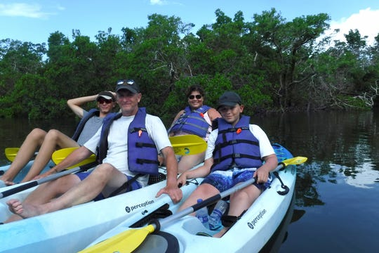 The Bell family, Gary and Kris with their sons Luke and Troy, came from England for a Marco vacation. While waters to the north suffer from red tide and blue-green algae blooms, waterways near Marco Island are clear, say kayak outfitters.