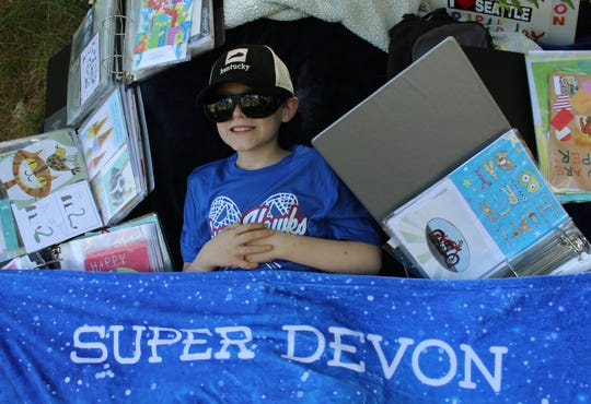 Devon Sweeney is surrounded by loose-leaf binders filled with the 1,500 cards he received for his 11th birthday.