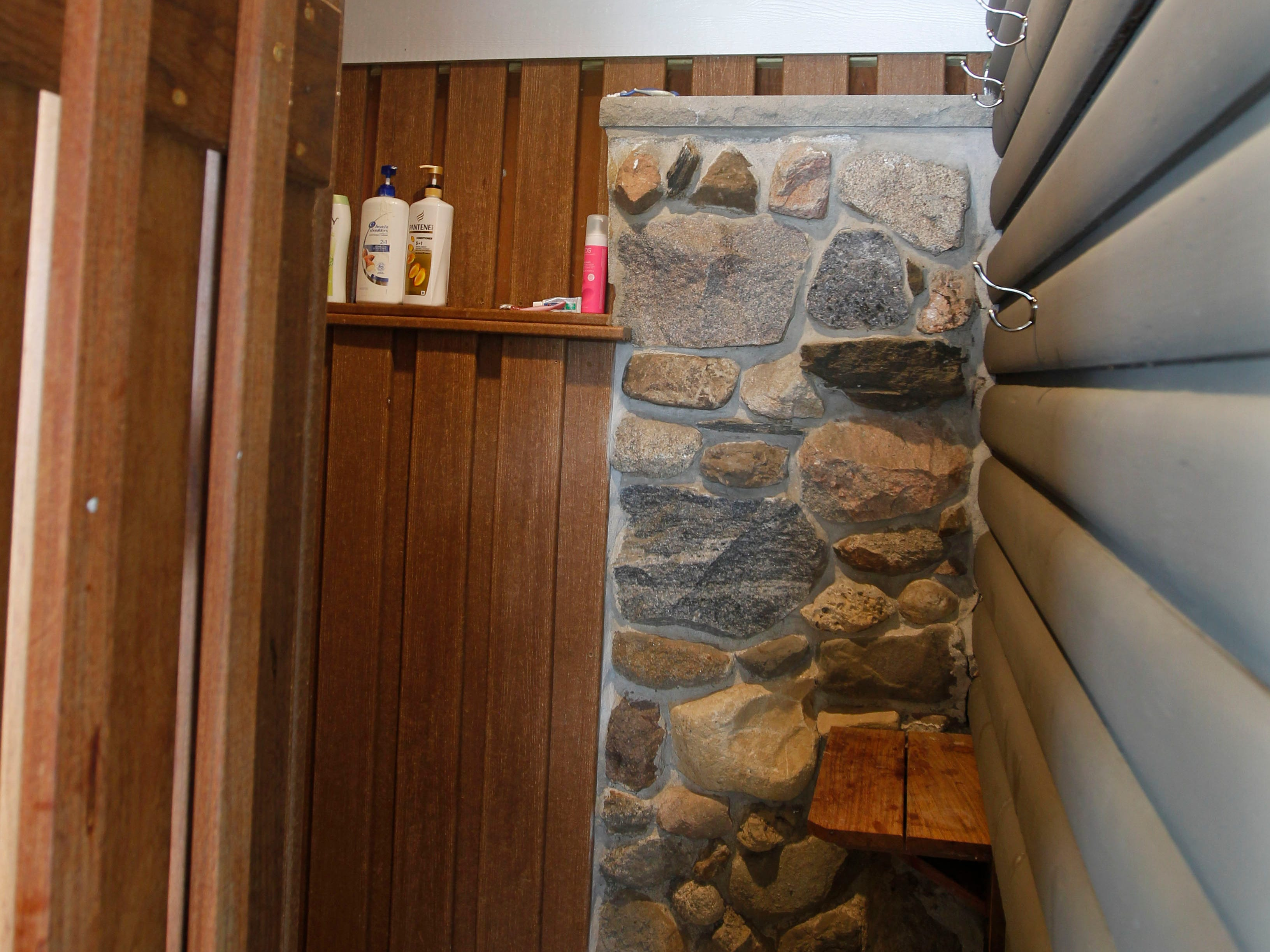 A shower is part of a recent addition to the Phillips family lake house. The rocks in the wall  were created to go with similar ones in the home's facade