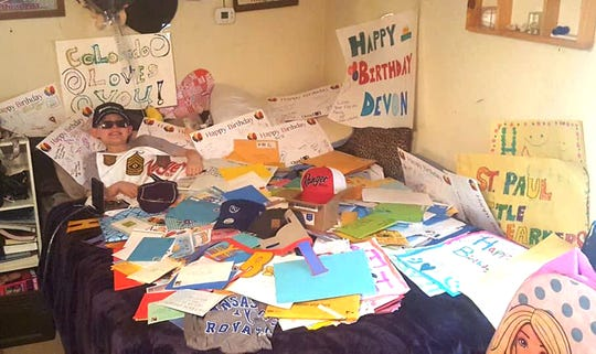 Devon lies under a pile of cards and letters he received on his 11th birthday. His family had hoped that he could receive a card from every state. Instead, he received more than 1,500 cards from all over the world.