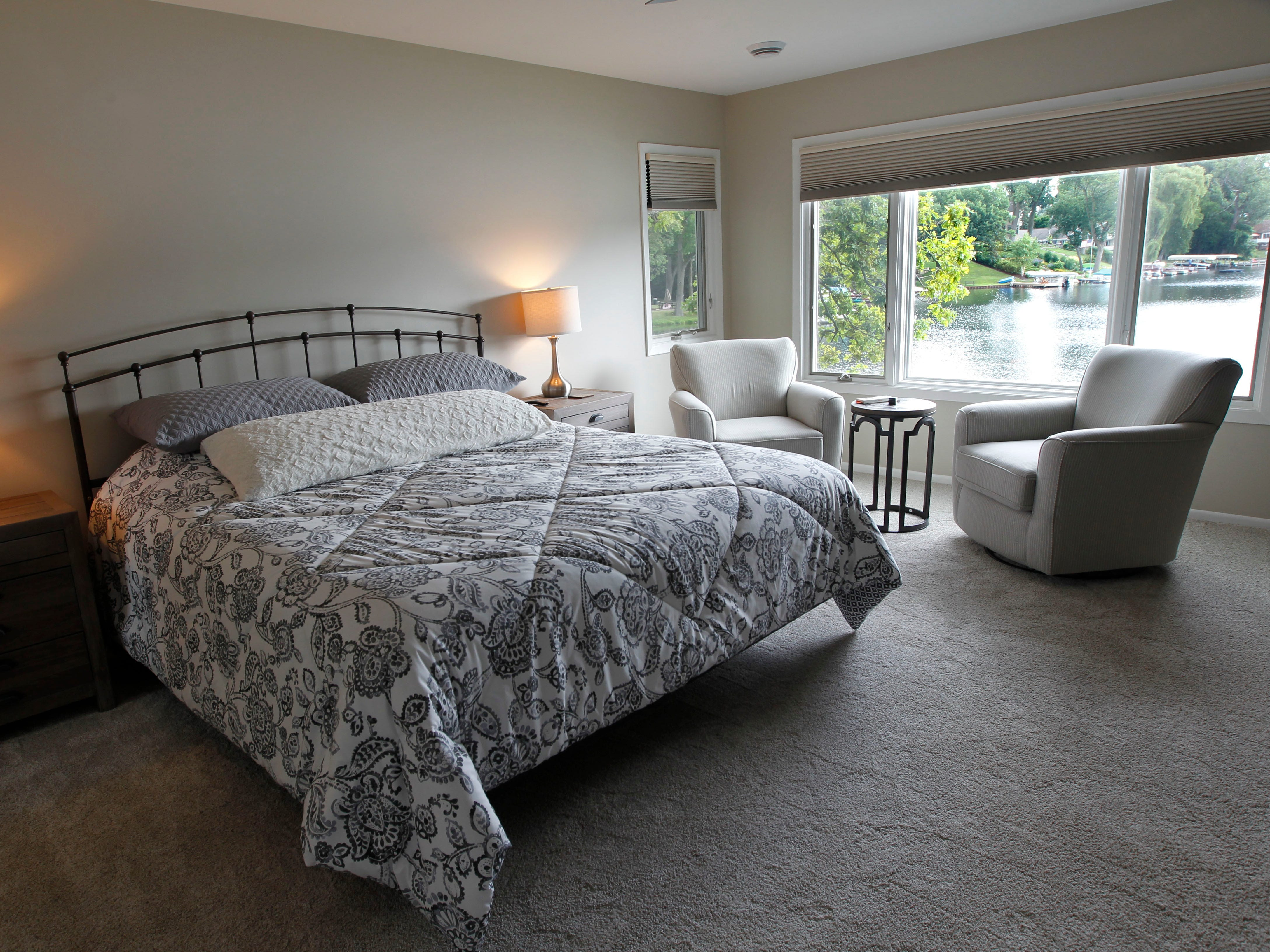 The guest room in the home has large windows for viewing the lake.