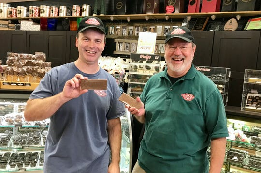 Northwoods Premium Confections owner Scott Lamoreux (left) with employee Mark Preuschl hold Beloit candy bars available in milk or 55% dark chocolate.