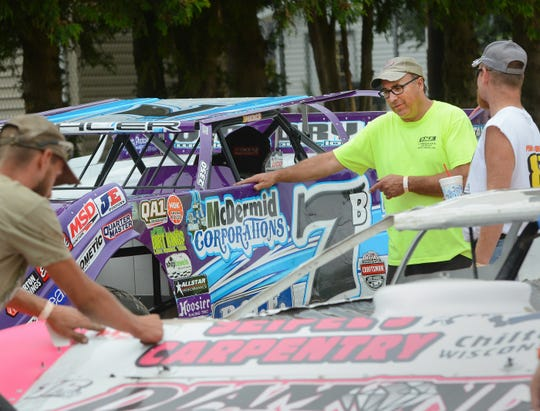 Driver Tim Buhler of Glenbeulah looks over his car Monday the Plymouth Dirt Track. Buhler, one of the track's top regulars, is competing along with the traveling World of Outlaws Late Model Series regulars.