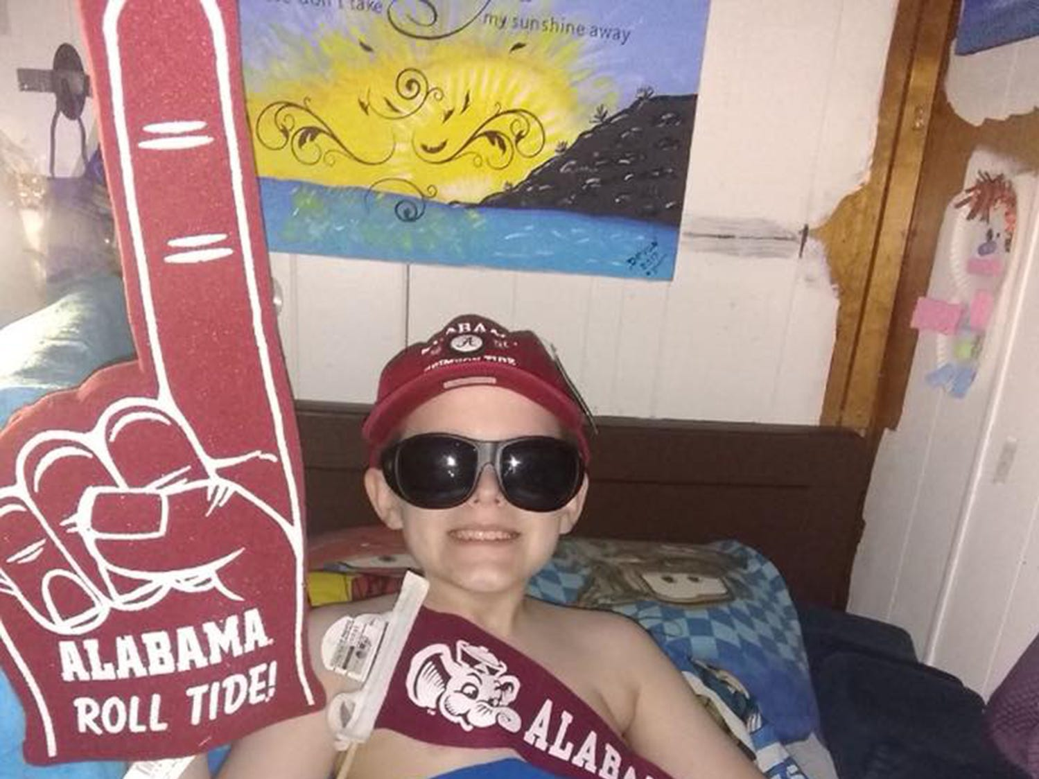Devon Sweeney displays swag sent to him by the University of Alabama in celebration of his 11th birthday. He must wear sunglasses because he eyes remain permanently dilated.