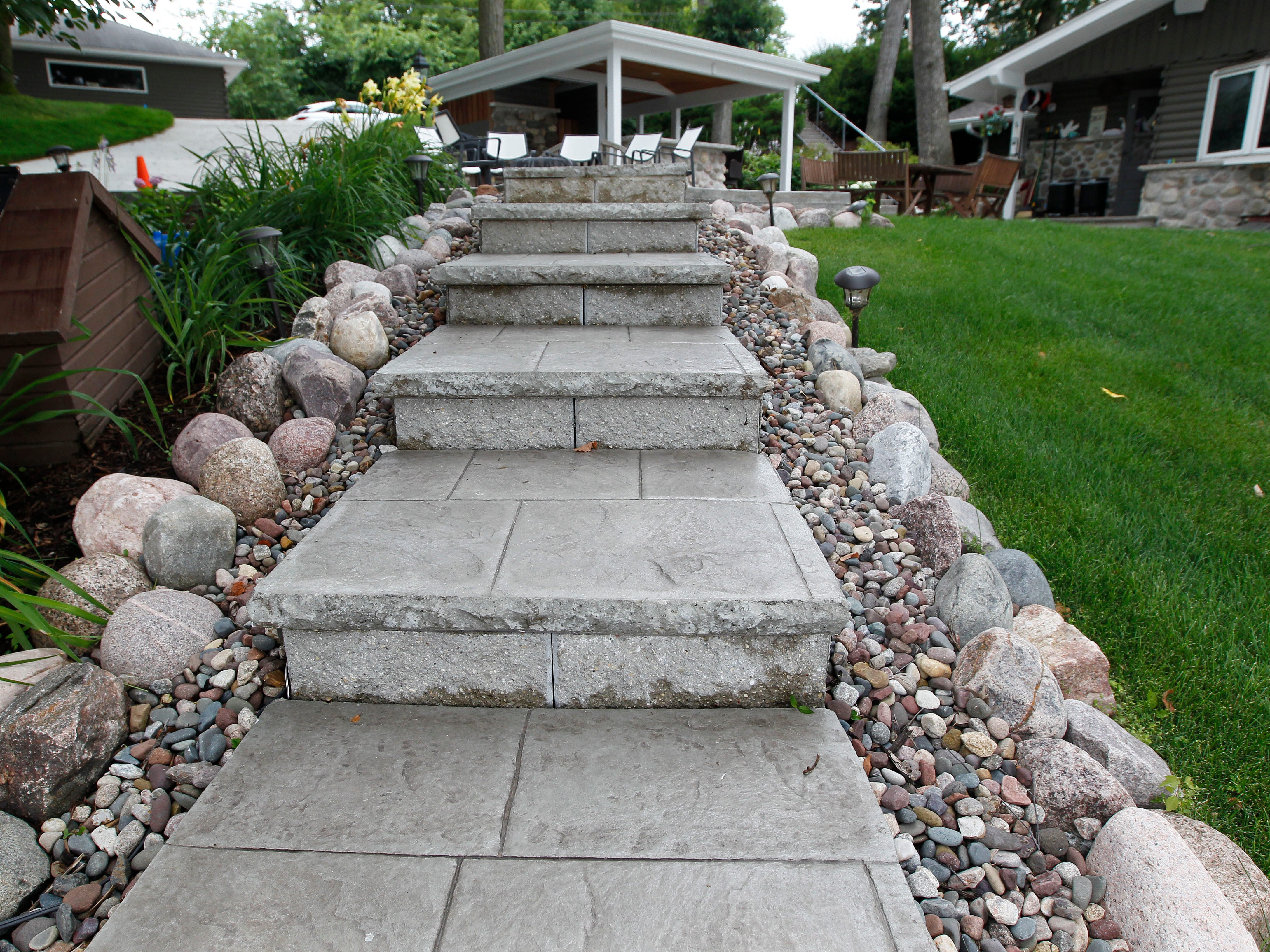 Stamped concrete stairs, dressed up with rocks, lead to the dock.
