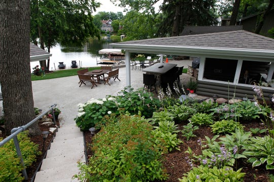 A staircase surrounded by plants leads to the patio area of the lake house. The boat house in the background is a kid's retreat with their friends.