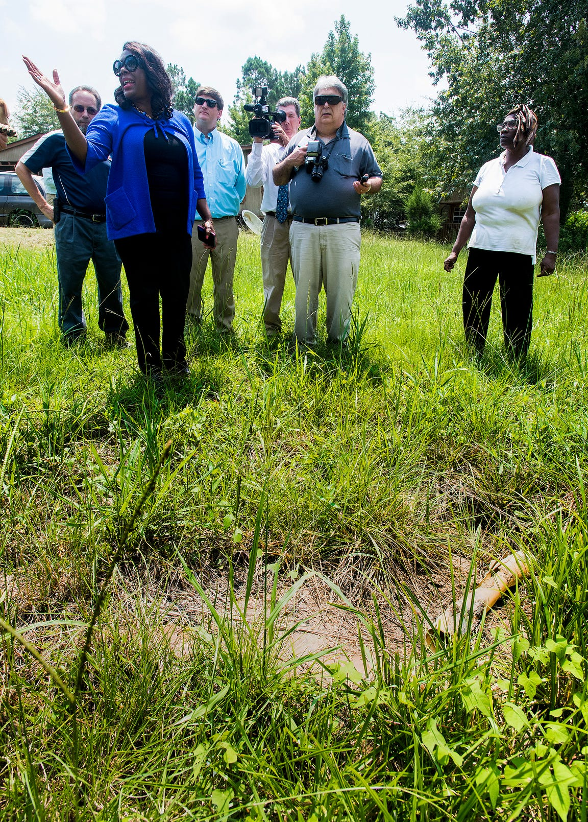 Congresswomen Terri Sewell, left, stands over a failed homemade septic tank in Farmersville, Ala., as she takes a group of engineering and health experts to homes with sewage problems in rural Lowndes County on Monday, July 30, 2018.