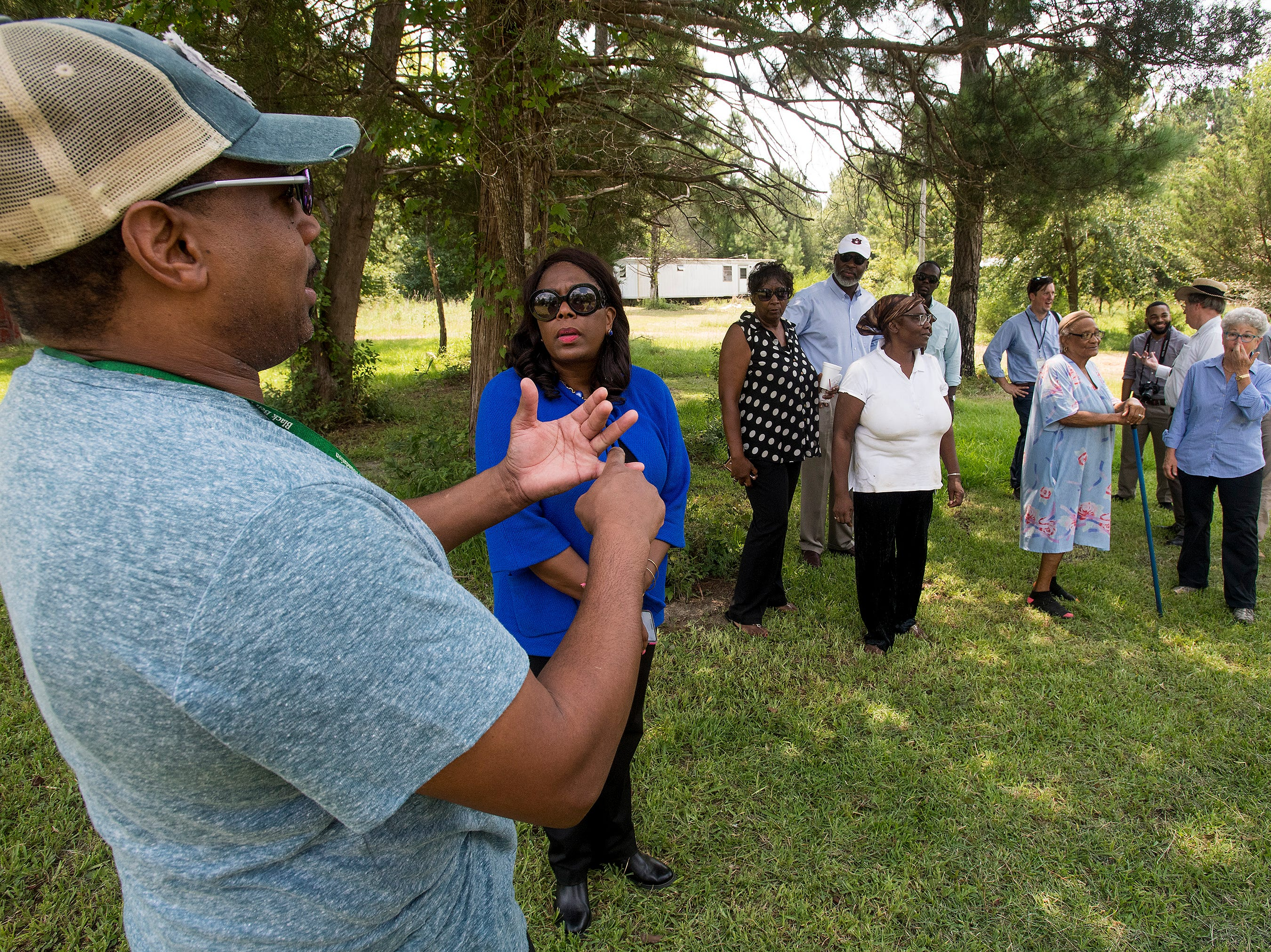 Congresswomen Terri Sewell talks with resident Tyrone Gulley as she takes a group of engineering and health experts to homes with sewage problems in Lowndes County, Ala., on Monday, July 30, 2018.
