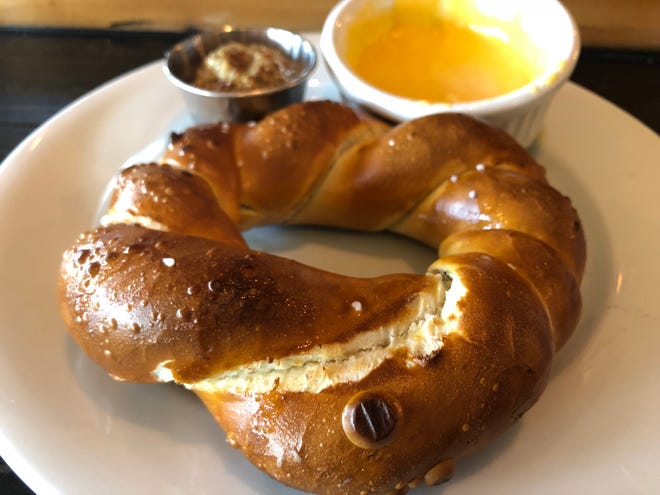 A custom-made pretzel in the shape of a wheel and a side of Cycle Crank IPA beer cheese and stone-ground pub mustard from Fit & Fuel Bicycle Cafe in North Naples.