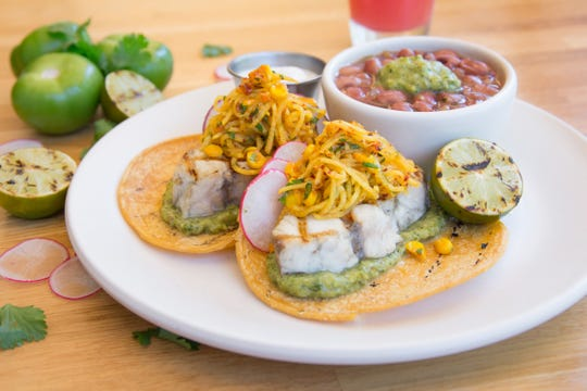 The gluten-free Summer Tacos at True Food Kitchen feature organic corn tortillas with grilled fish or grass-fed steak topped with a seasonal jicama slaw, tomatillo avocado salsa, and a dollop of citrusy, dairy-free coconut-lime yogurt served alongside flavorful Anasazi beans.