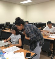 Idali Gil, 18, of Passaic recieves help from Nedia Morsy in filling out a state financial aid application. This year wil be the first time immigrants without lawful status will be able to apply for state financial aid to help pay for tuition at colleges in New Jersey.