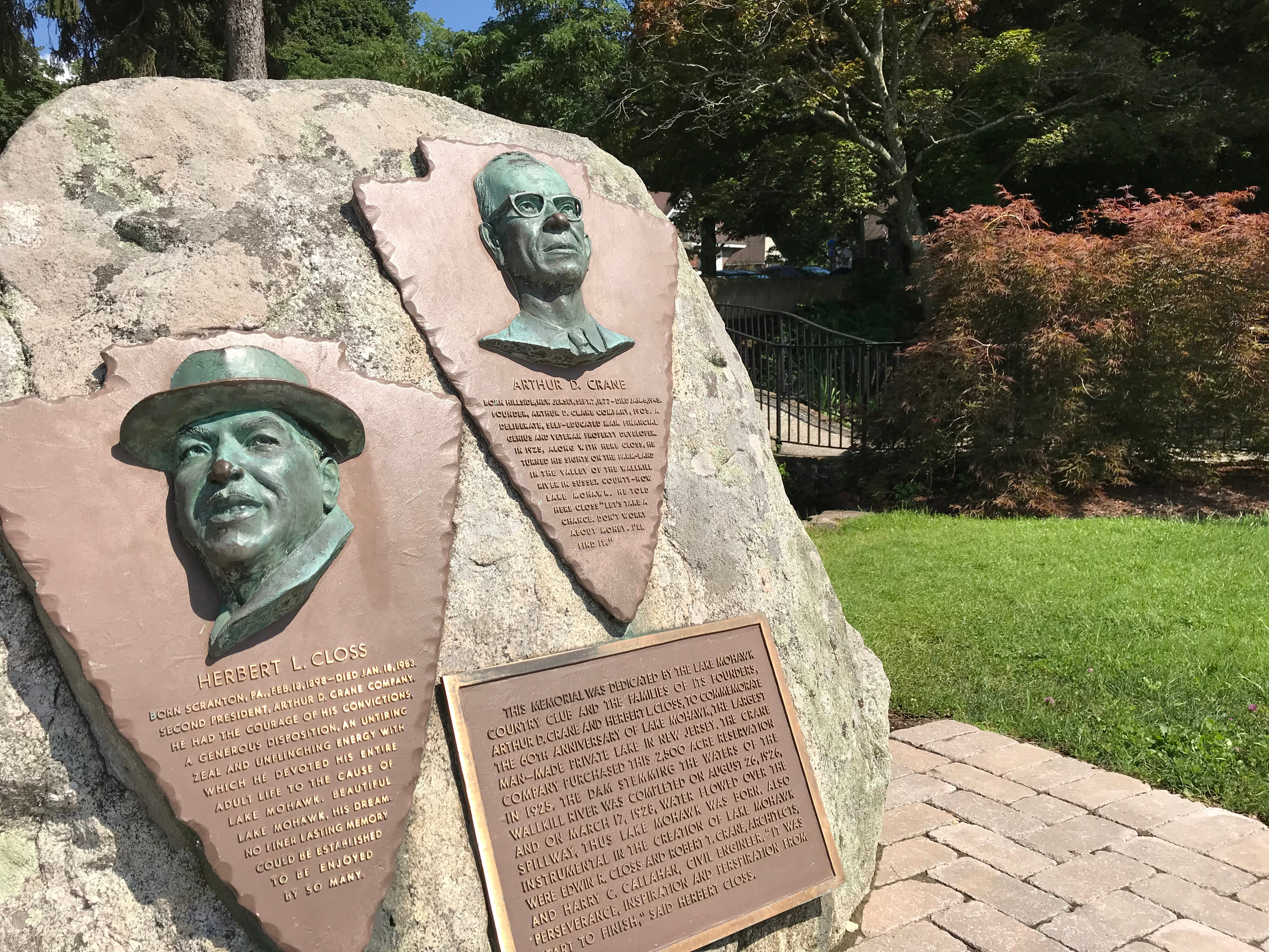 A stone with a trio of plaques near the shore of Lake Mohawk in Sparta, N.J. on July 26, 2018, honors the lake community's developers Arthur Crane and Herbert Closs.