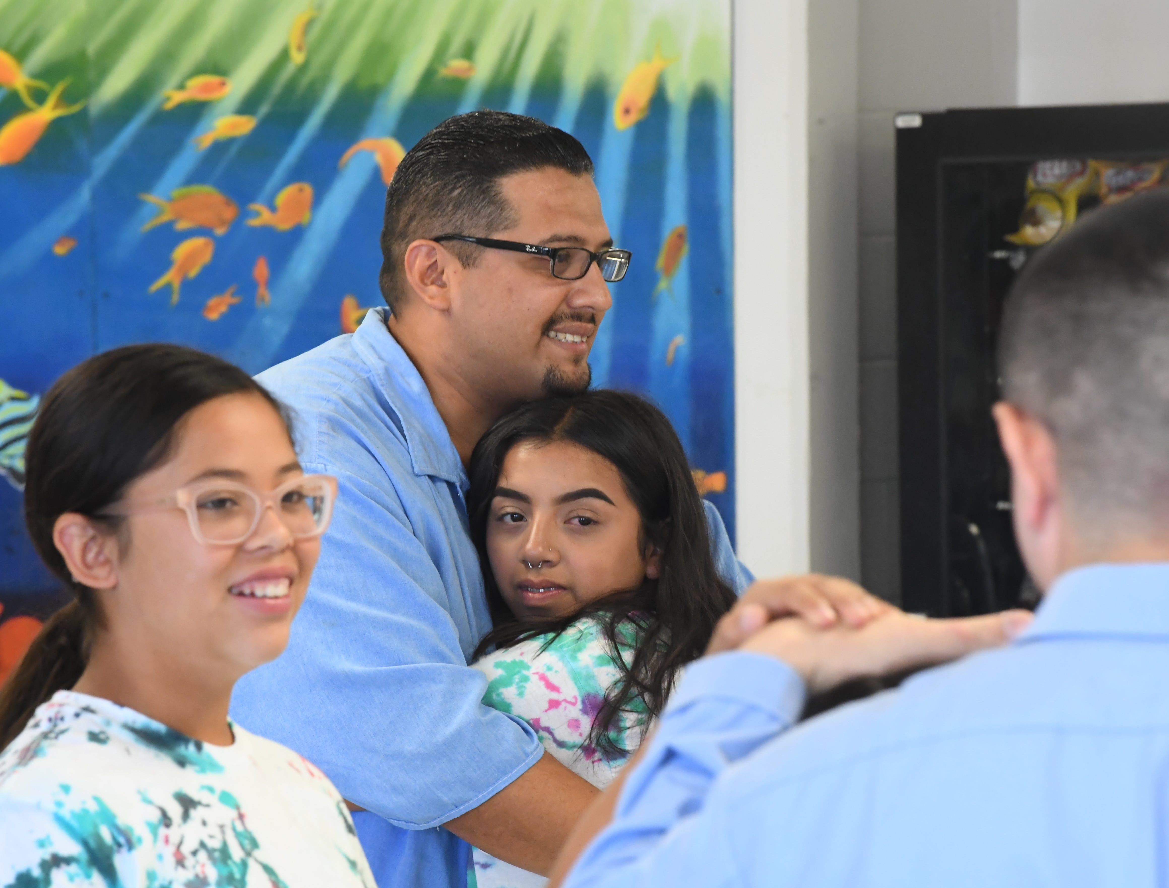 Alex Garcia, 31, hugs his daughter Angelina Garcia, 14, at Camp Grace Friday.