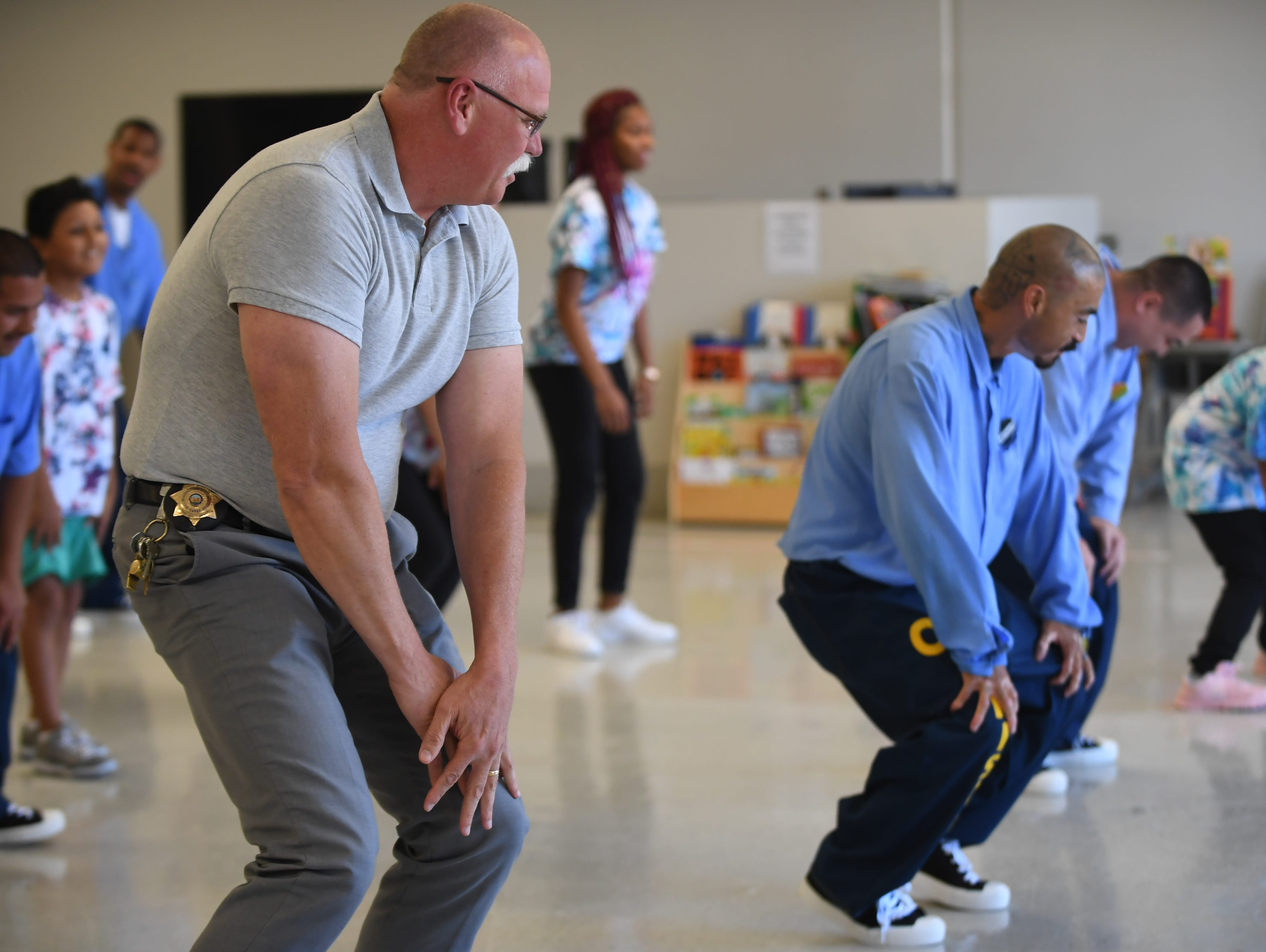 Salinas Valley State Prison Warden Shawn Hatton dances alongside inmates and their kids at Camp Grace Friday.