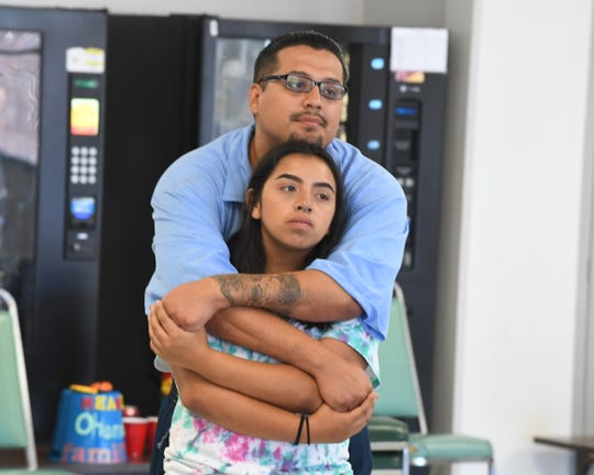 Alex Garcia, 31, holds his daughter Angelina Garcia, 14, at Camp Grace Friday.