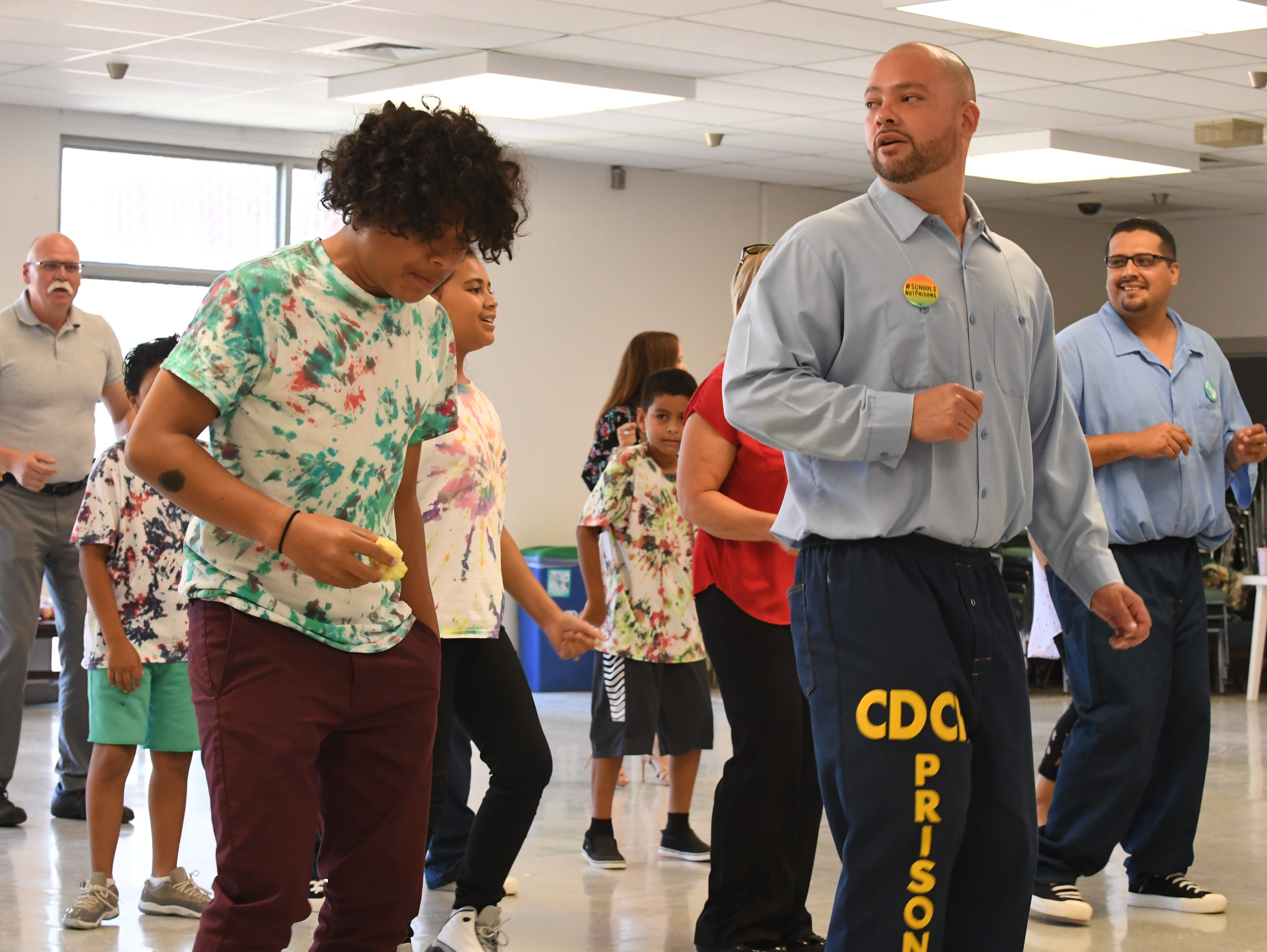 Inmates and their children, as well as staff, dance to the Cupid Shuffle at Camp Grace Friday.