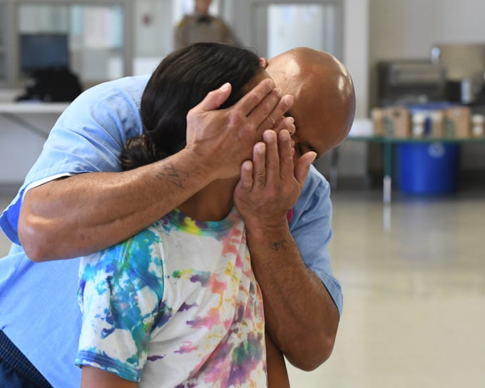 A Salinas Valley State Prison inmate embraces his daughter Friday at Camp Grace.