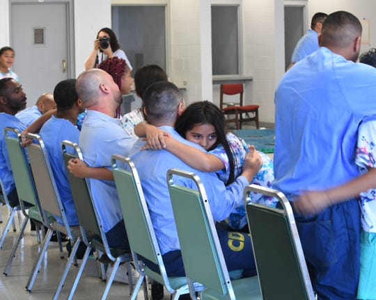 A girl hugs her father during Camp Grace at Salinas Valley State Prison Friday.