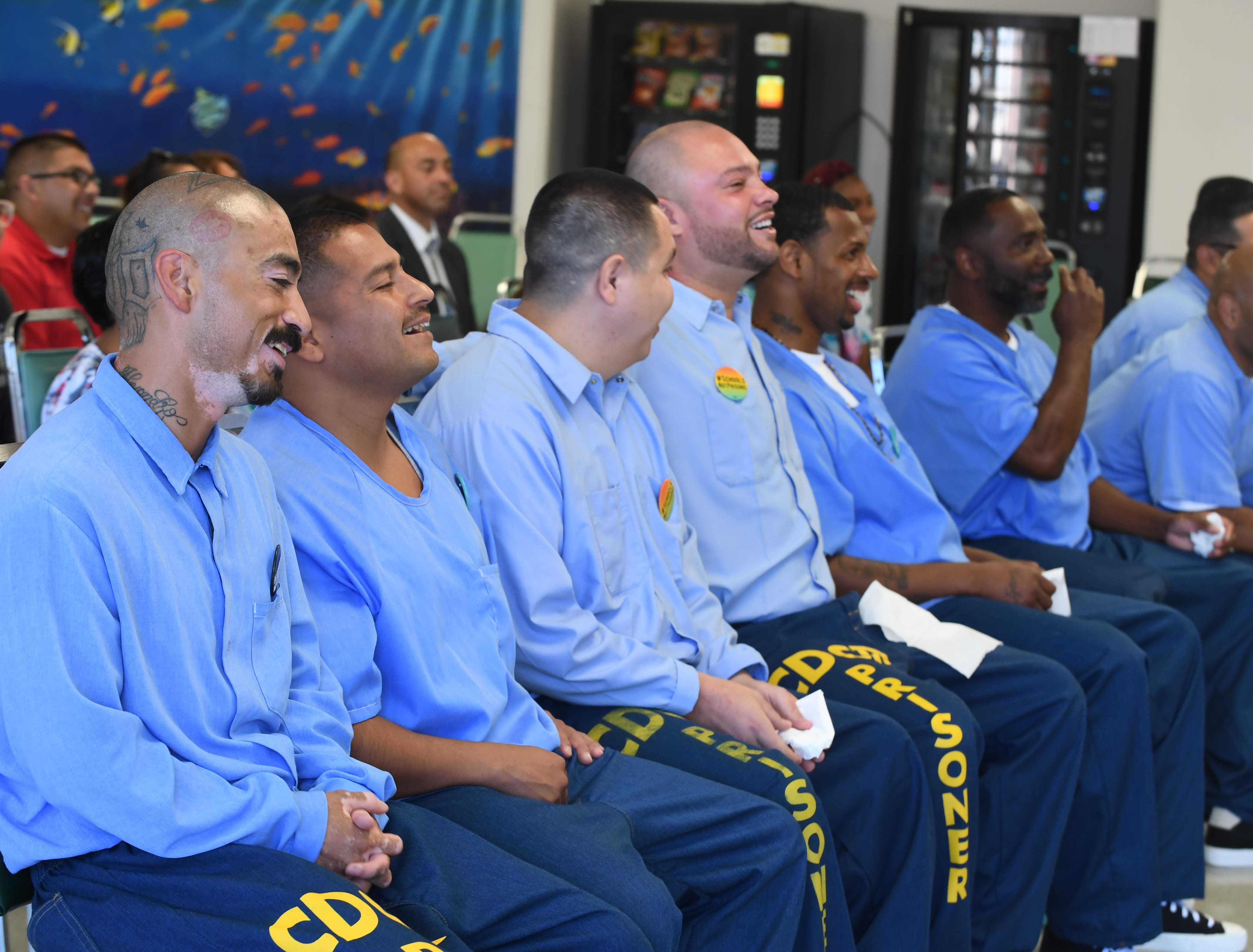 Salinas Valley State Prison inmates laugh as their children take turns telling jokes at Camp Grace Friday.