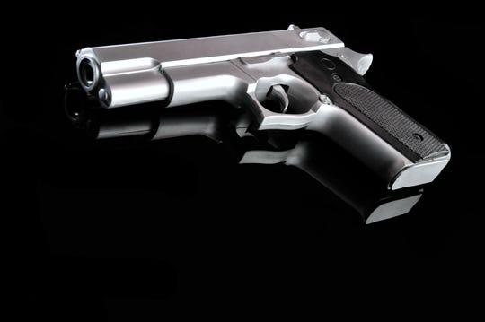 Gun on reflective black surface.