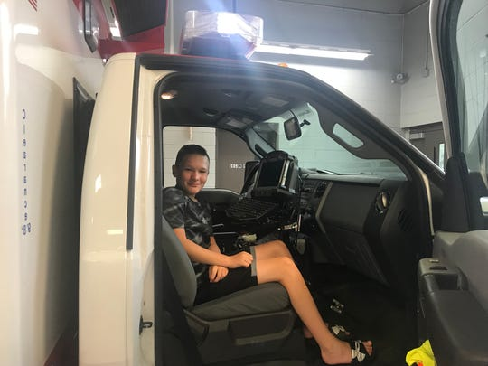 """Brendan Conway in an ambulance after Nanuet Community Ambulance Corps honored him with a """"life-saving"""" award for saving his father's life with an EpiPen after his father was stung multiple times by hornets and had a severe allergic reaction."""