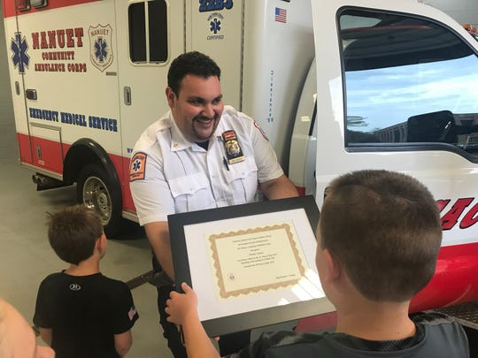 """Assistant Chief John Delgado presenting a """"life saving award"""" to Brendan Conway, 13, for saving his dad's life after he was stung multiple times by hornets and had a severe allergic reaction."""