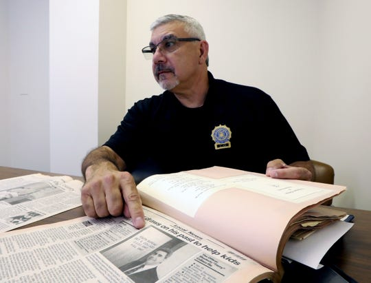 Haverstraw Police Detective Terry Collazo looks over a scrapbook of his 31 years on the job July 30, 2018. He retired at the end of June.