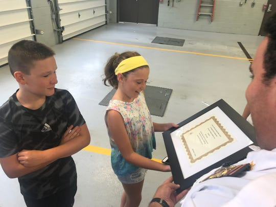"""Assistant Chief John Delgado presenting a """"life saving award"""" to Katie Conway, 12, for saving her dad's life after he was stung multiple times by hornets and had a severe allergic reaction. Her brother Brendan was also given the honor."""