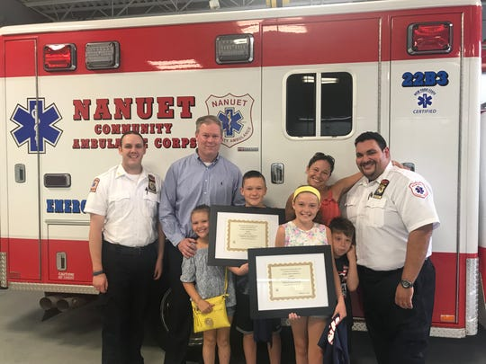 """The Conway family --(from left) Michael, Caroline, Brendon, Kristie, Katie and Michael -- with the chief, Chris Dunlavey, and assistant chief, John Delgado, of the Nanuet Community Ambulance Corps. The first responders presented Brendon, 13, and Katie, 12, Conway with """"life saving award"""" after they helped save their father's life when he was stung multiple times by hornets and had a severe allergic reaction."""