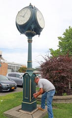 Bob Dawson, a custodian with the Town of Ramapo checks the inside of the clock on Route 45 in Spring Valley on July 30, 2018.