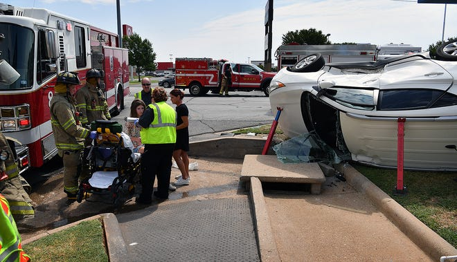 Emergency medical personnel examine the driver of a white Hyundai following a two-vehicle accident at Kemp Boulevard and Fleming near Pier 1 Imports Monday morning. There were no seious injuries in the accident.