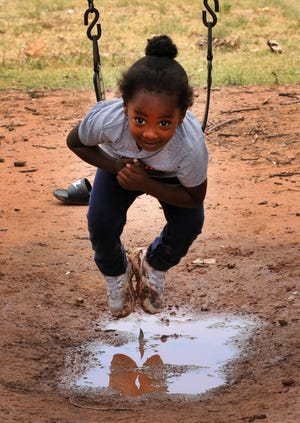 2-year-old, Langston Thorton uses a swing to dabble her feet in a rain puddle, Monday afternoon as the area enjoyed cooler temperatures.
