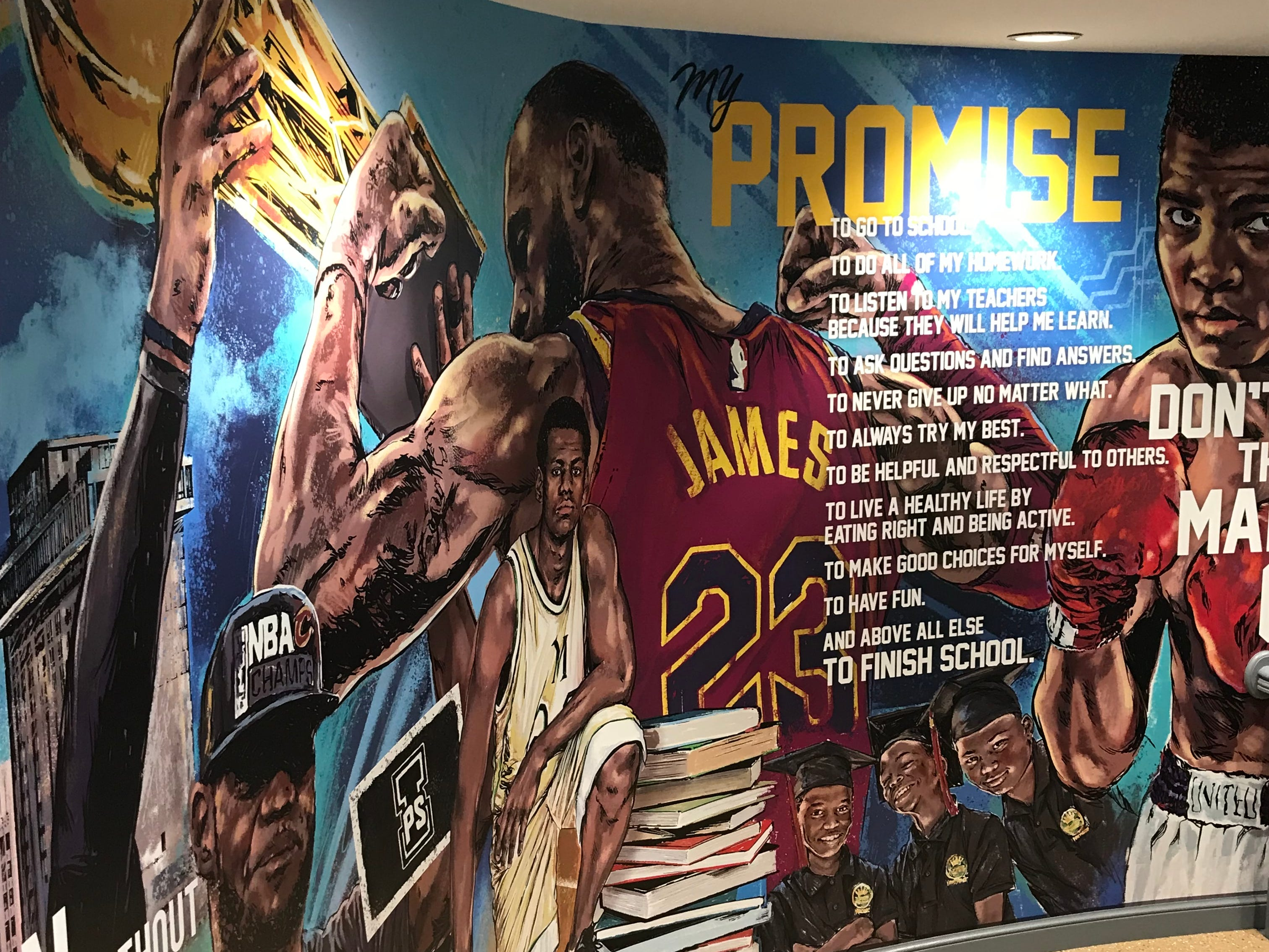 A mural includes depictions of LeBron James and Muhammad Ali, along with the school's mantra.
