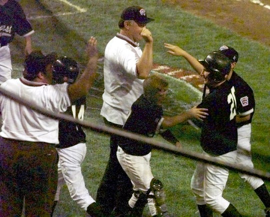 (PSPORTS) ASBURY PARK PRESS PHOTO BY THOMAS P. COSTELLO - - - 8/24/98 - - - Toms River East American players and coaches congratulate Gabe Gardner (#20) after his fifth inning three run homeragainst the Cypress Federal team from Cyprus, CA, during Tuesday nights game at the Lamade Stadium in South Williamsport, PA.