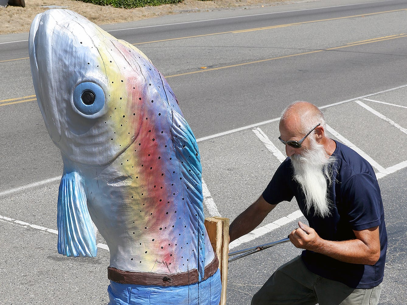 The Kingston troll statues have found a new home, at the Kingston Mercantile & Marine on Highway 104. Original carver Terry Tessmer from Central Point, Oregon, uses a tire lug wrench to bolt a refurbished one in position along the highway in front of the store,