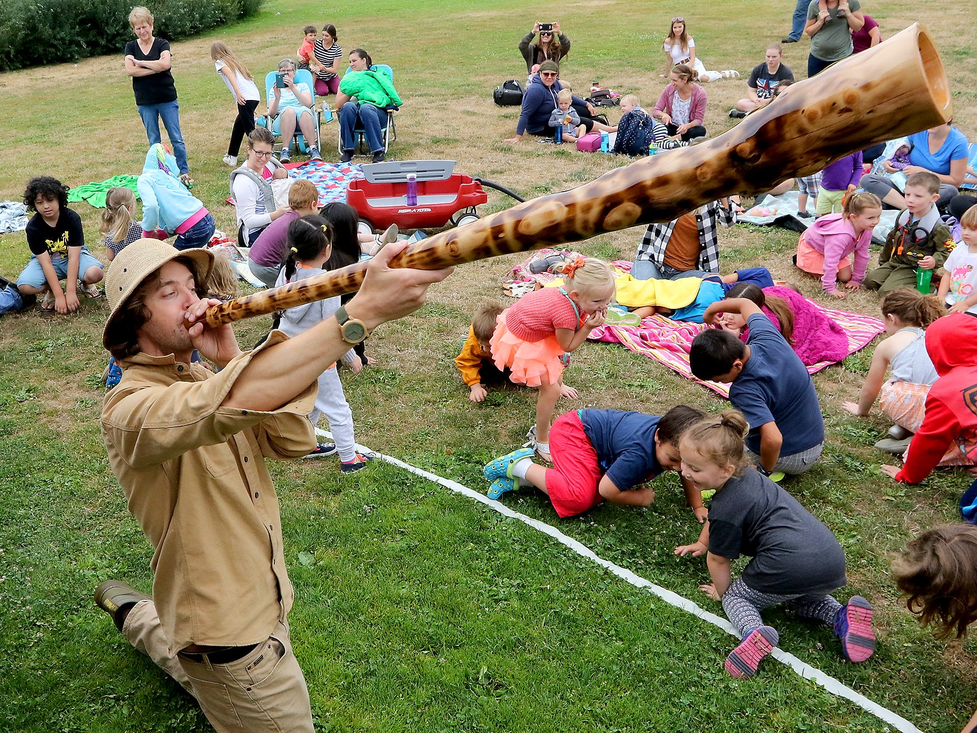 Youngsters spin around and play the part of Australian animals while William Thoren plays the didgeridoo as part of his Didgeridoo Down Under presentation for those gathered at Blueberry Park in Bremerton on Tuesday, July 31, 2018. The program was sponsored by the Kitsap Regional Library.
