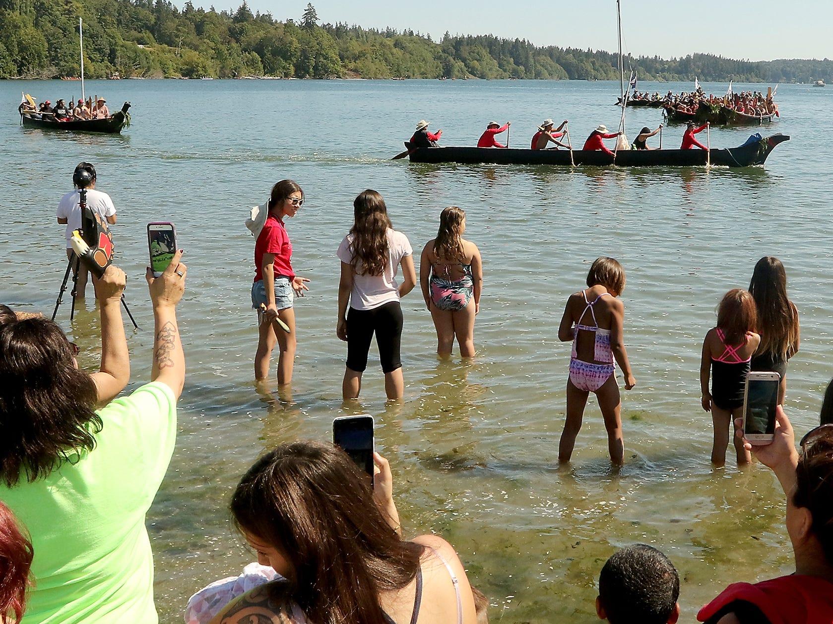 Tribal Canoe Journey ÒPaddle to PuyallupÓ canoes parade past those on shore of Point Julia on Tuesday, July 24, 2018.