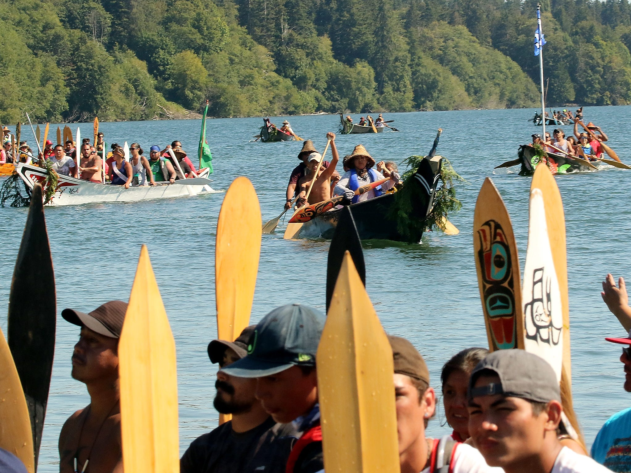 Tribal Canoe Journey ÒPaddle to PuyallupÓ canoes head for the shore to ask and await permission from the Port Gamble S'Klallam Tribe to come ashore at Point Julia on Tuesday, July 24, 2018.