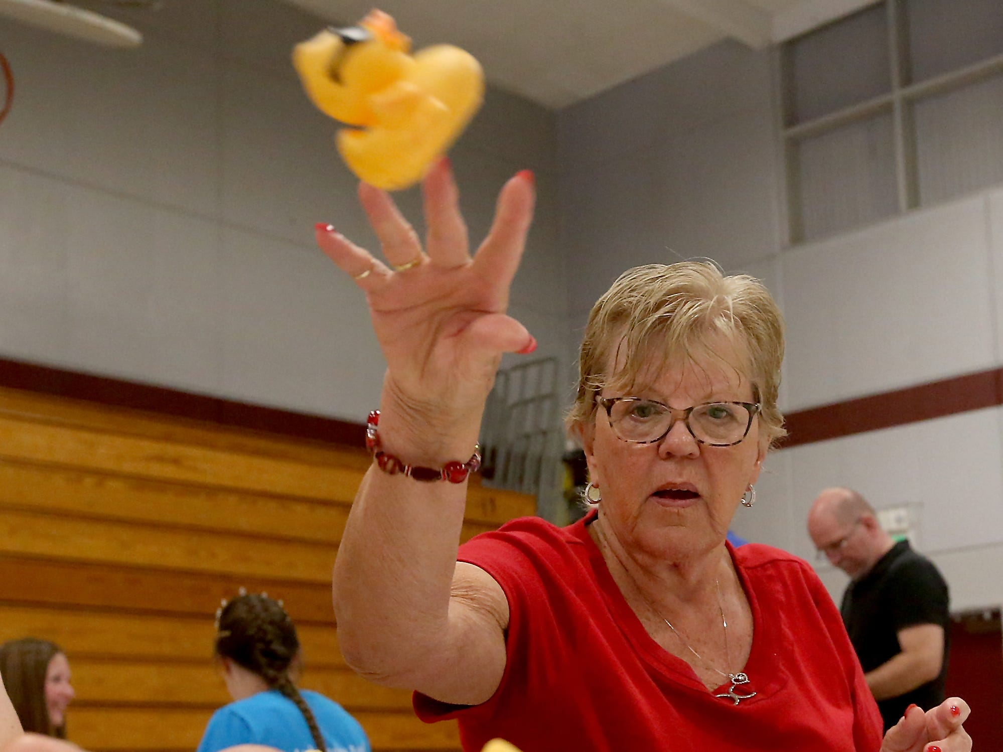Silverdale Rotarian Sharon McGavick tosses a rubber duck into the air and toward the finished duck box after sticking a new raffle number on it for the upcoming Silverdale Rotary Duck Race, at Central Kitsap Middle School in Silverdale on Thursday, July 26, 2018. The 25th Anniversary Silverdale Rotary Duck Race takes place on Sunday at Silverdale Waterfront Park.