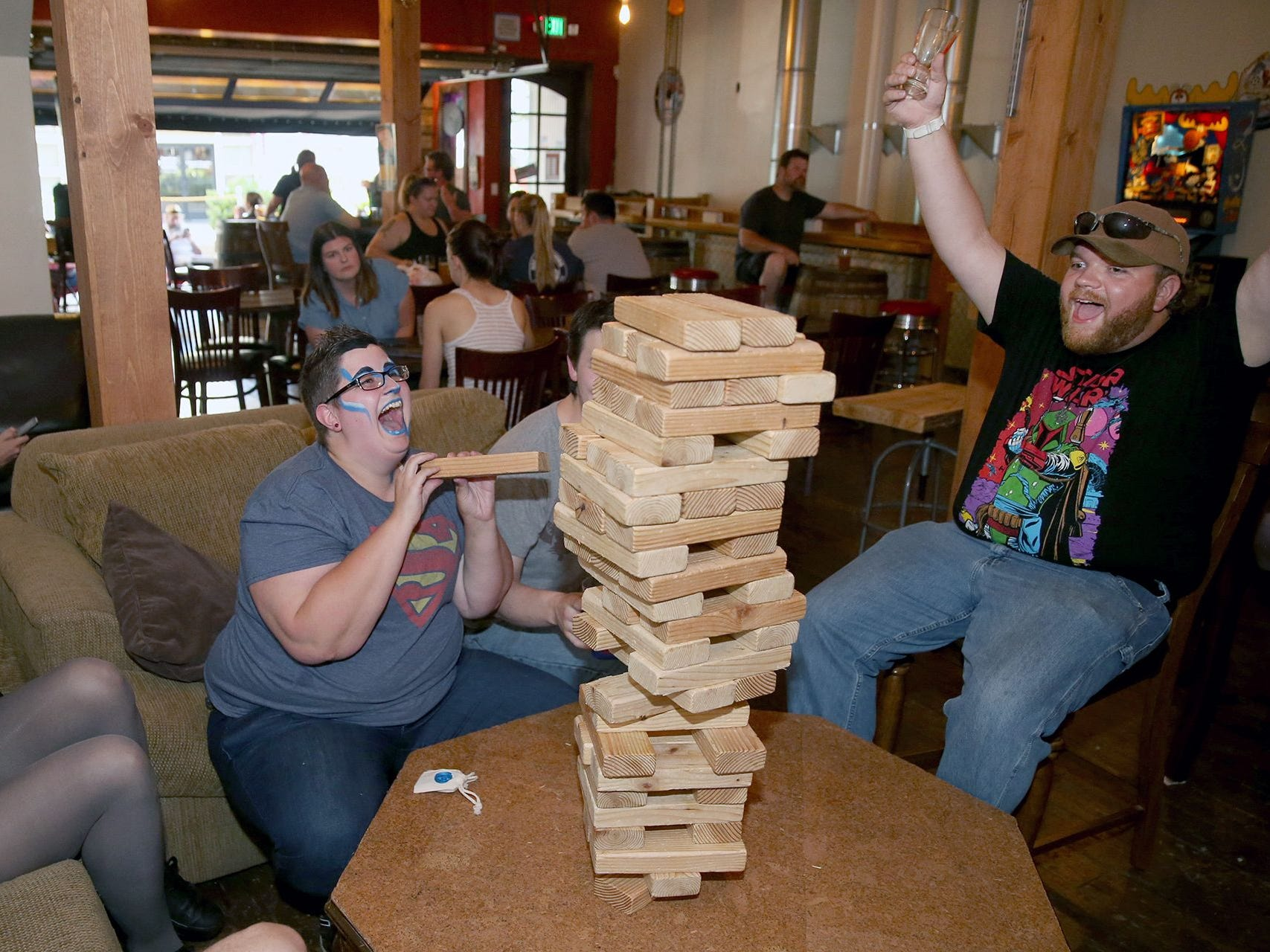 Jenga players (left to right) Katelyn Ziegenhagen, Nic Shakley, and Zach Siltanen celebrate Shakley's move at Dog Days Brewing during the 2018 Nerd Crawl in downtown Bremerton on July 26, 2018.