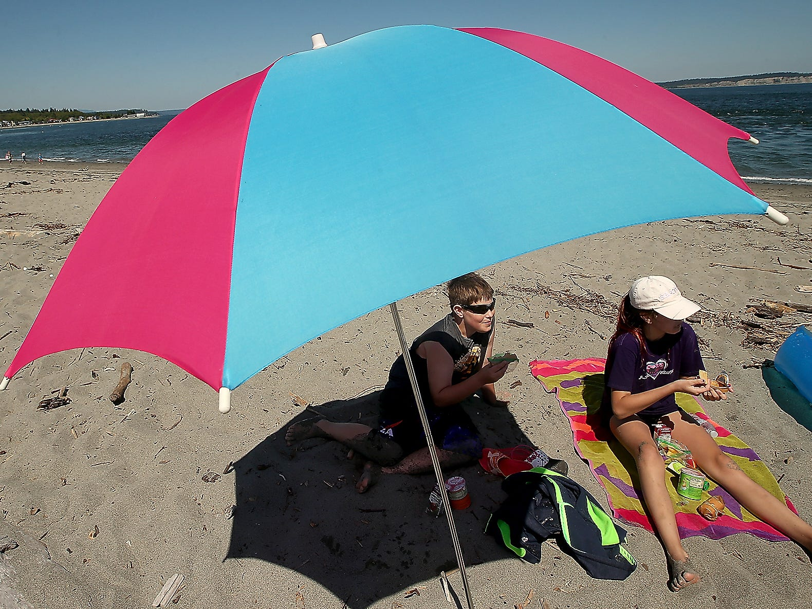 Siblings Tyler, 11, and Ashlee Verkest, 12, eat their lunch near the shade of their beach umbrella at Point No Point in Hansville on Tuesday, July 24, 2018.