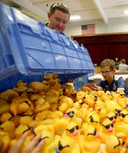 Silverdale Rotarian Ryan Gilhuly (left) dumps a tub of rubber ducks on a table while volunteer Aidan Haro, 13 (right) and Max Billingsley, 13, (not pictured) try to keep them from spilling onto the floor, as Rotarians and volunteers remove old numbers from the ducks and stick new ones on at Central Kitsap Middle School in Silverdale on Thursday, July 26, 2018. The 25th Anniversary Silverdale Rotary Duck Race takes place on Sunday at Silverdale Waterfront Park.
