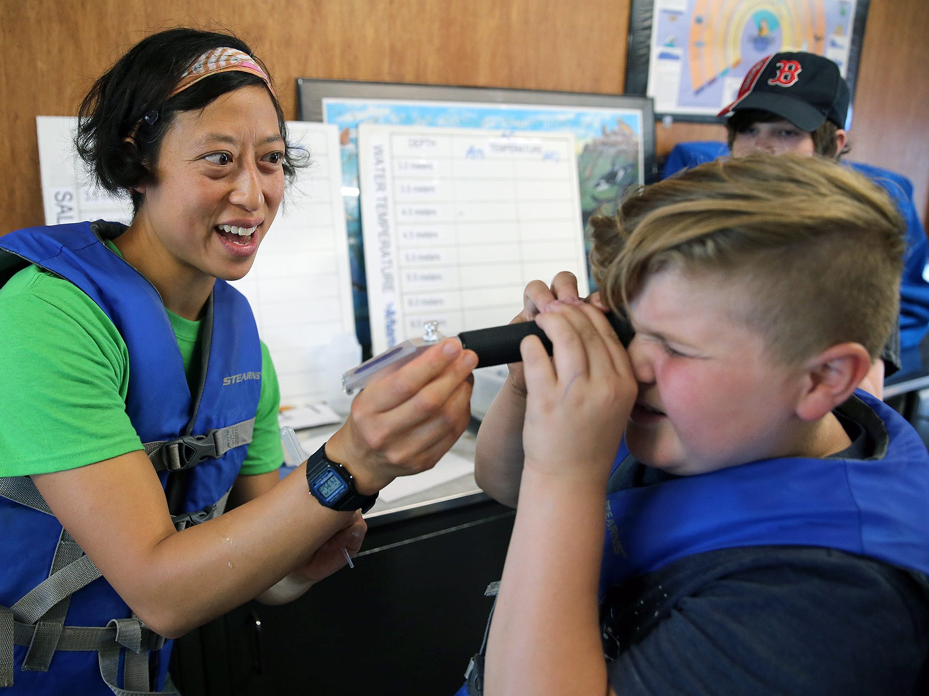 Sylvia Yang, the SEA Discovery Center Director, shows cybersecurity student Quentin Clark, 12, from Bainbridge Island, how to view a salt water sample. Western Washington University is hosted a free cybersecurity camp for middle schoolers at at the SEA Discovery Center in Poulsbo from July 23-27.